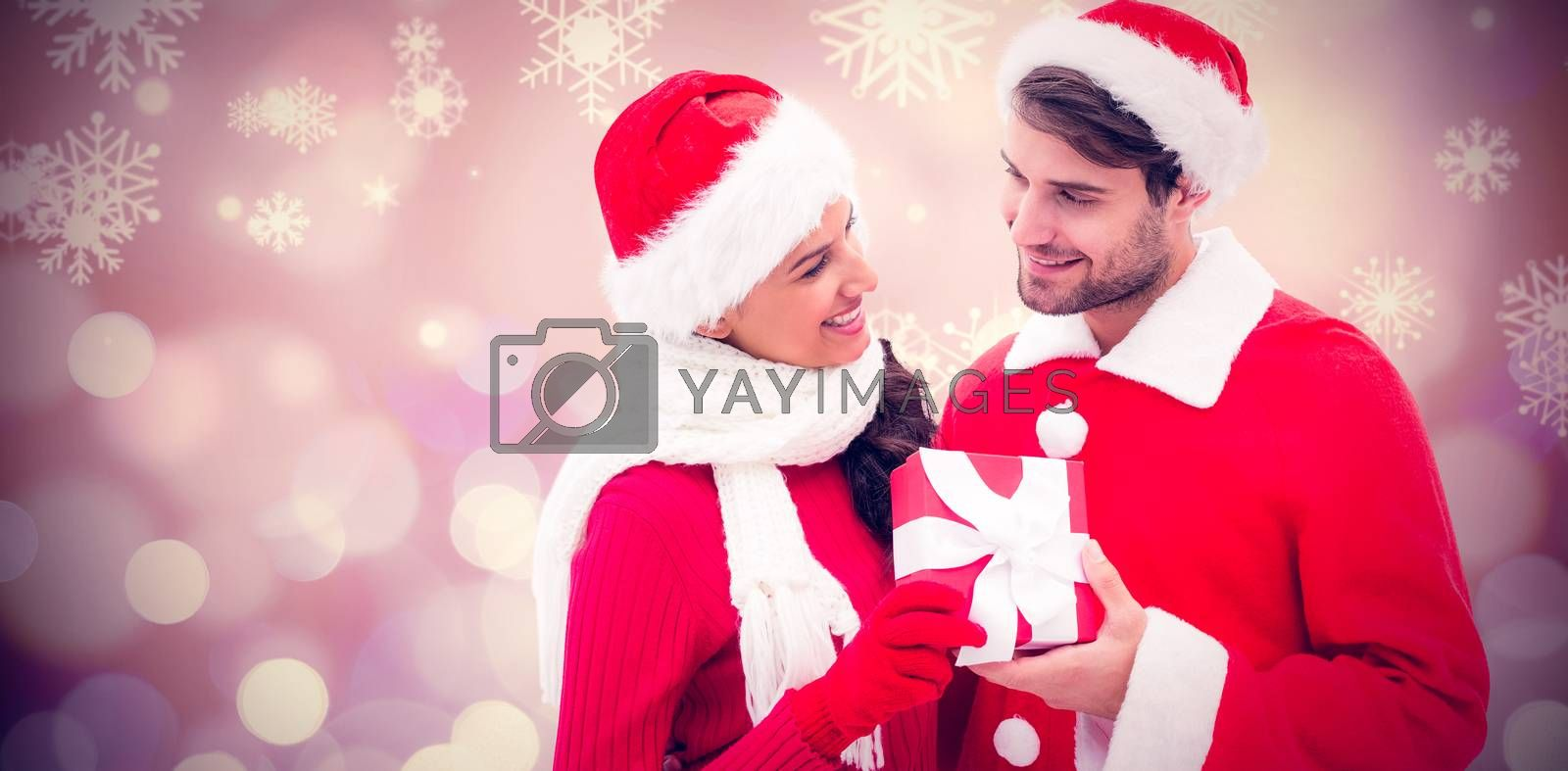 Festive young couple holding gift against glowing christmas background