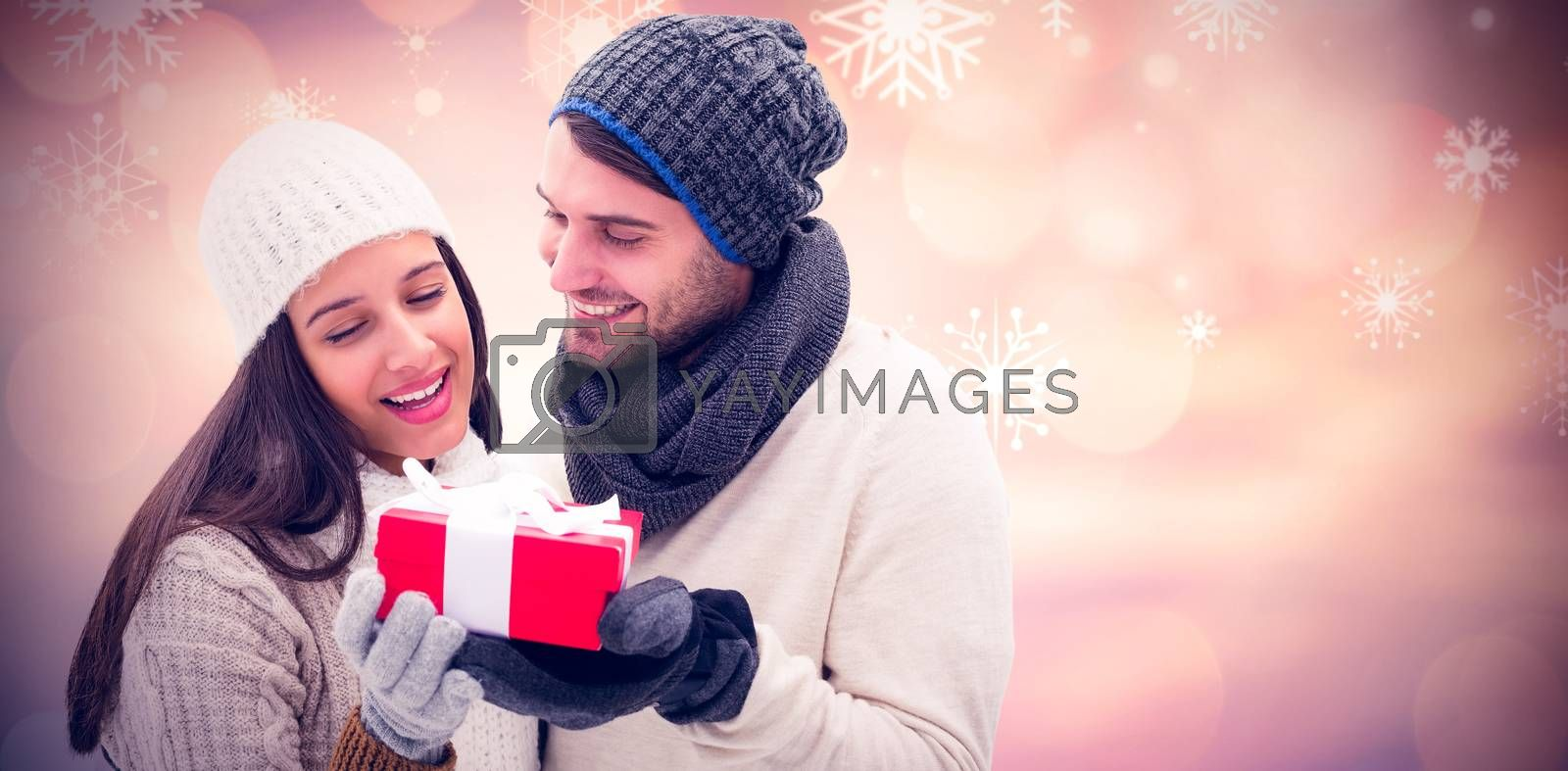 Winter couple holding gift against glowing christmas background