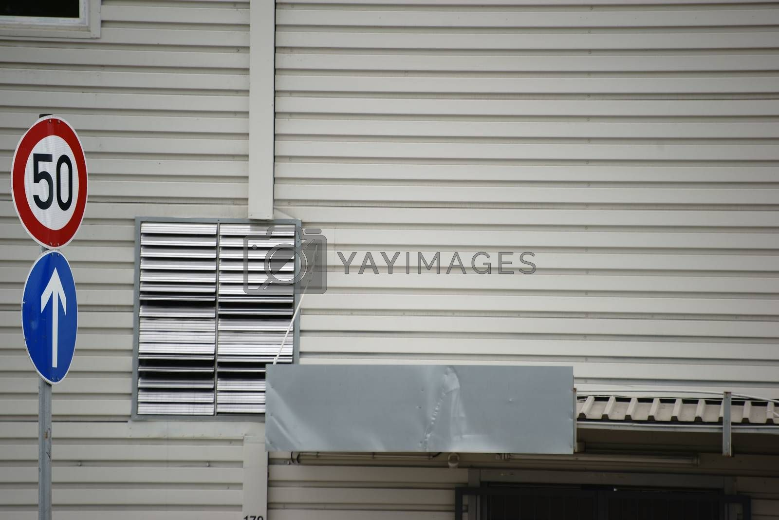 Roof boards and a ventilation grille with stainless steel on a wall of a public shopping building.