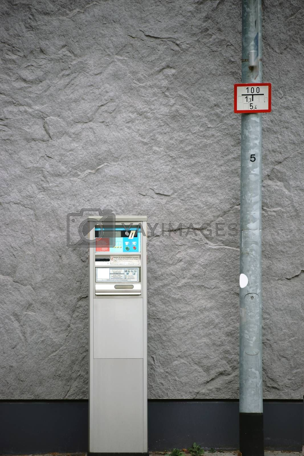 An old ticket machine or parking meter is facing a striking wall.