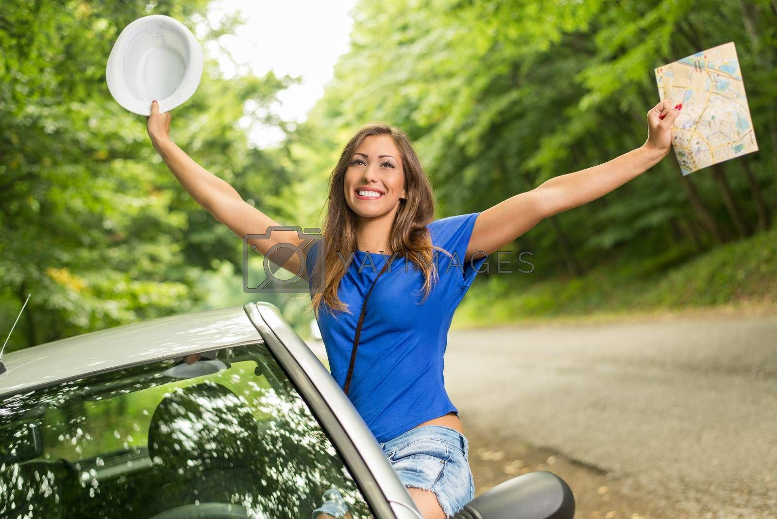 Cheerful woman on summer travel vacation leaning out of a car window. She is holding map with arms raised.