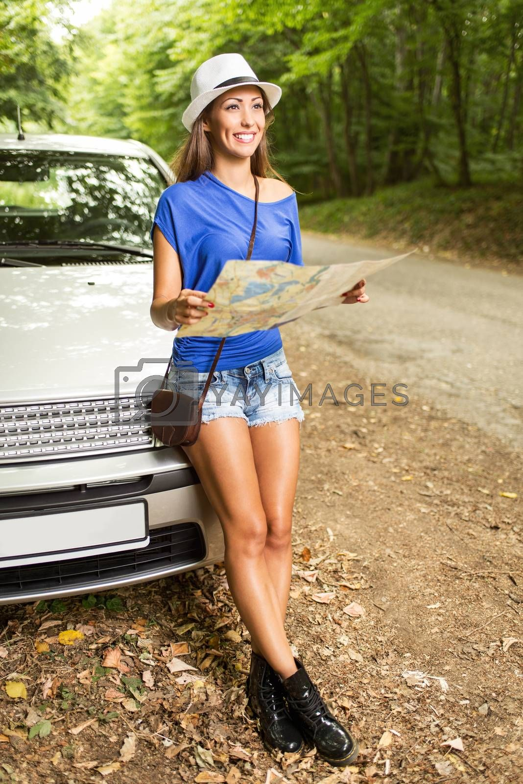 Young beautiful woman standing before a car in the forest, holding map and looking at destination.