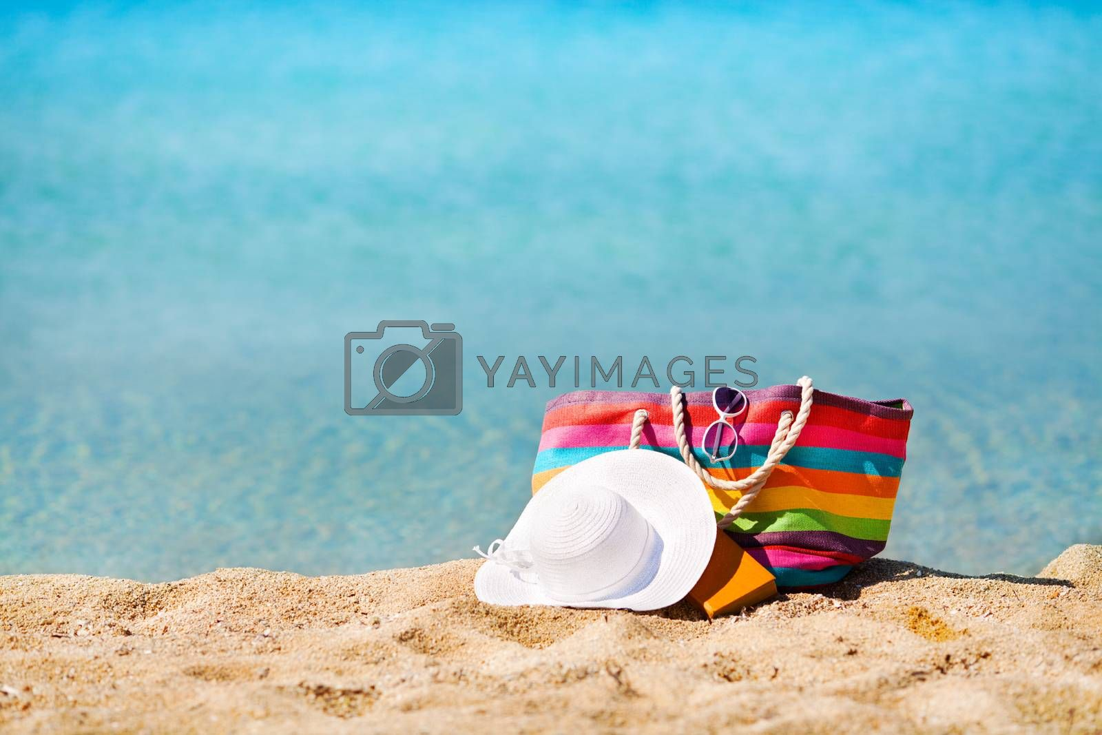 Multi Colored bag and white hat on the beach