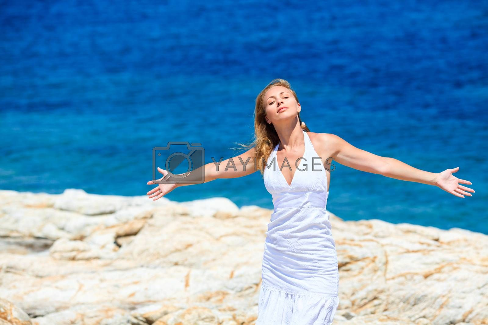 Young beautiful woman enjoying and relaxing on the rock with open arms