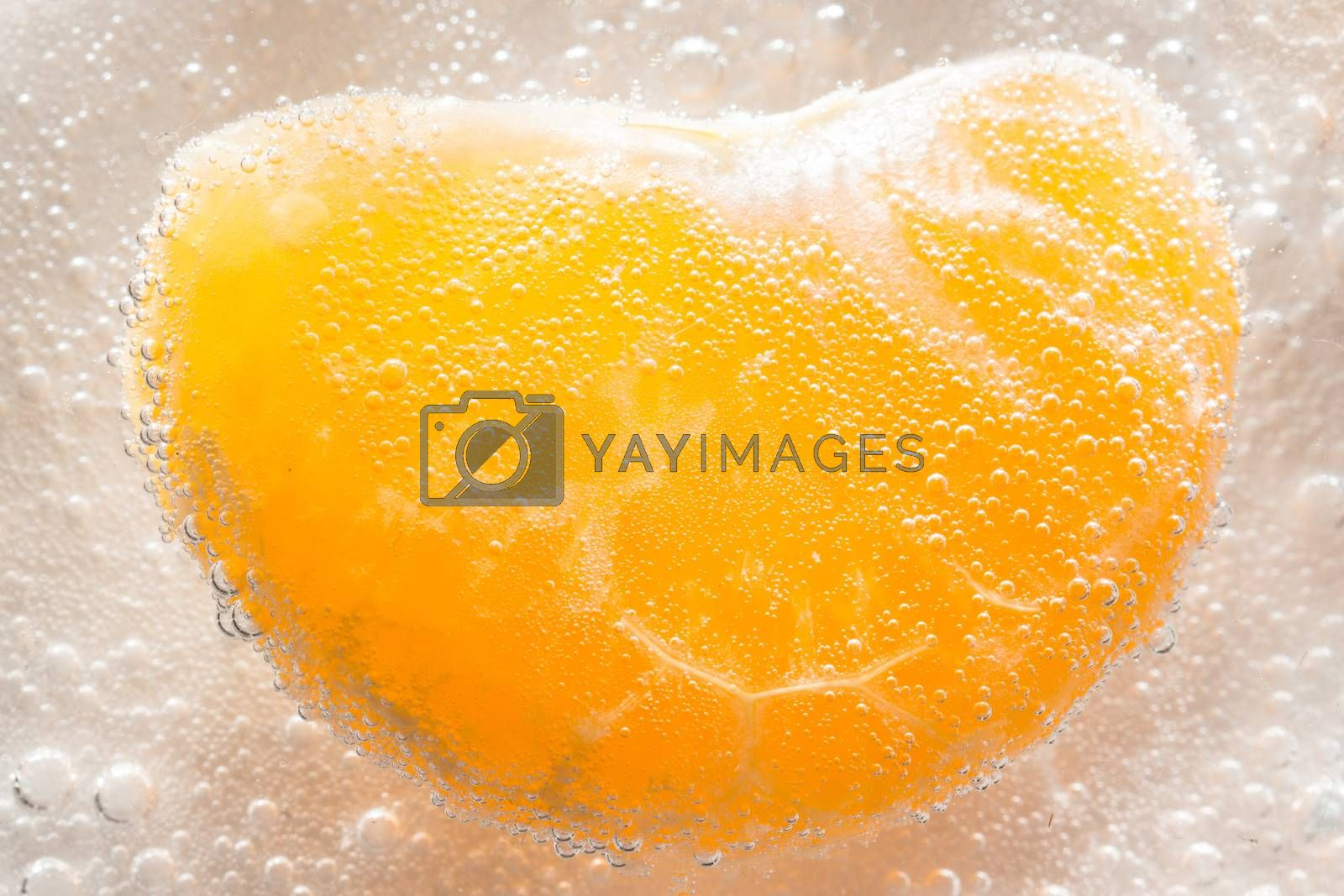 The photo depicts a tangerine in bubbles