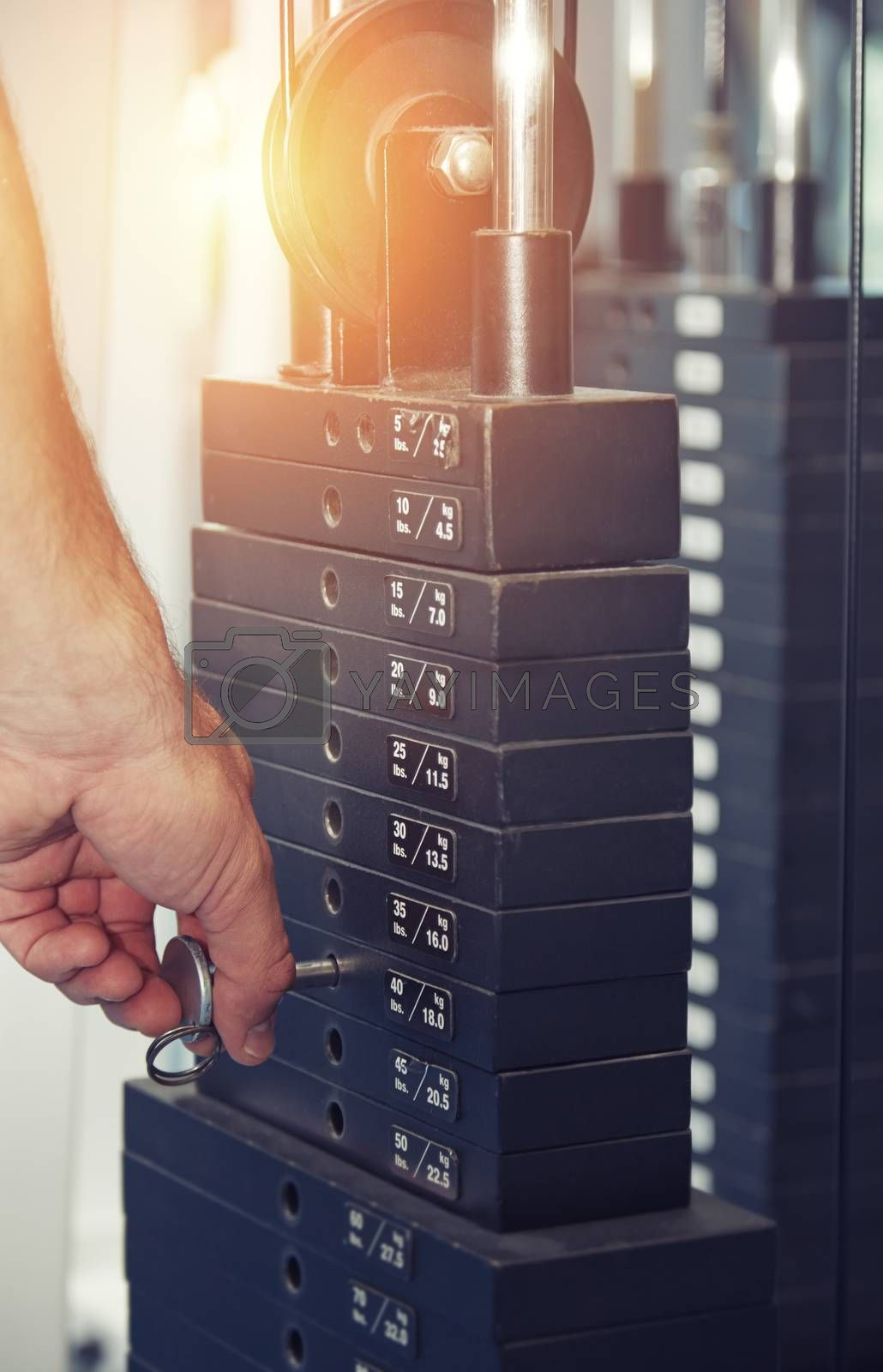 Hand of man adjusting the weight in exercise machine