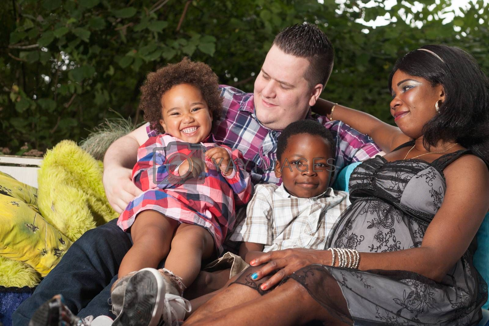 African family is sitting on the couch in the garden