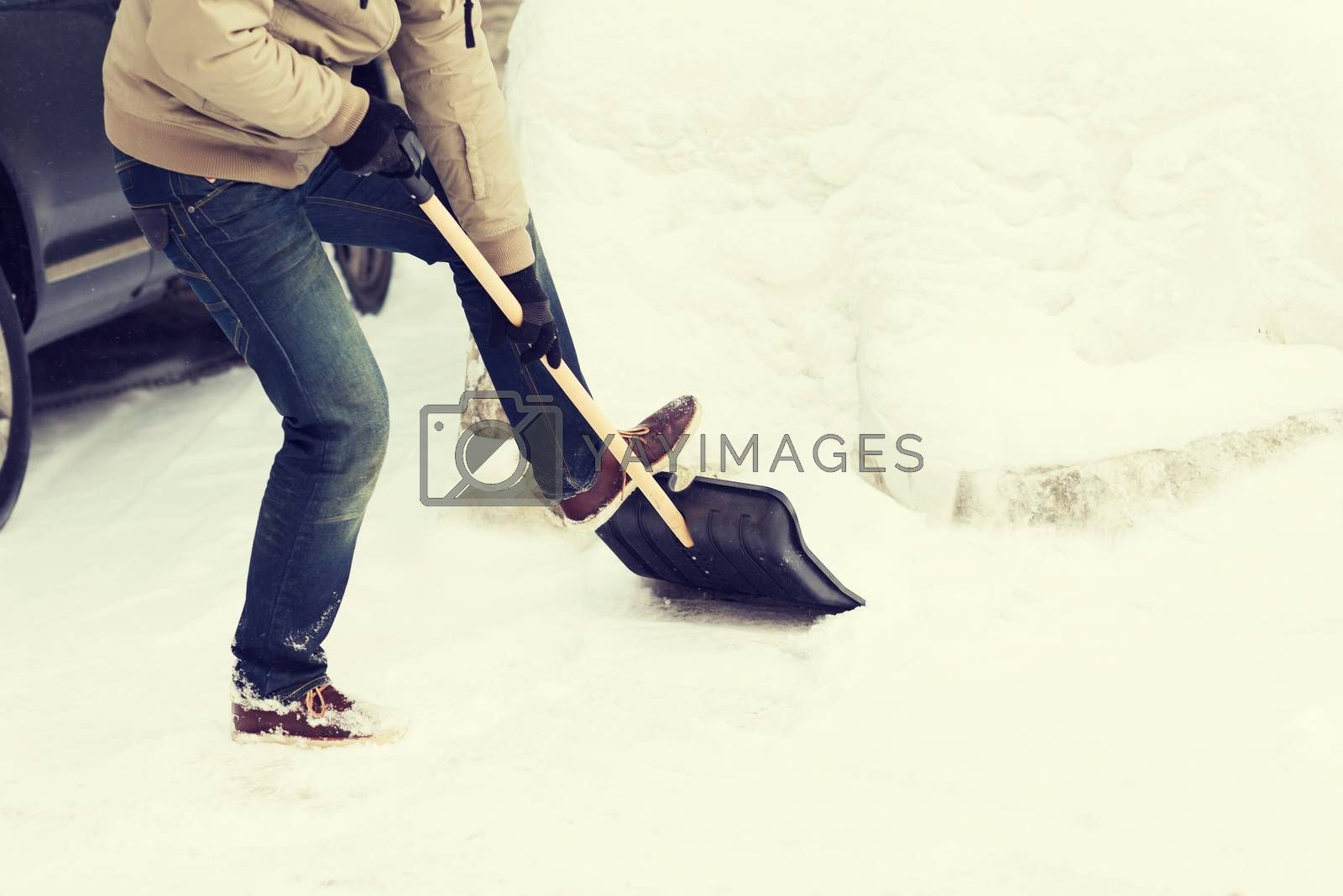 winter and cleaning concept - closeup of man shoveling snow from driveway