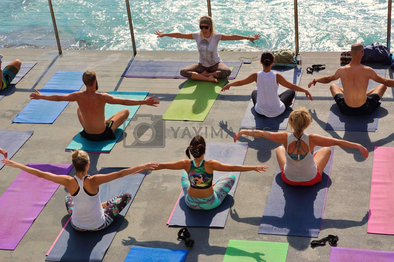 BONDI, AUSTRALIA- OCTOBER 25, 2015;  Yoga by the beach Bondi.   Yoga class beside the pool at Bondi Icebergs, Bondi Australia.  Participants perform yoga moves outdoors by the sea.