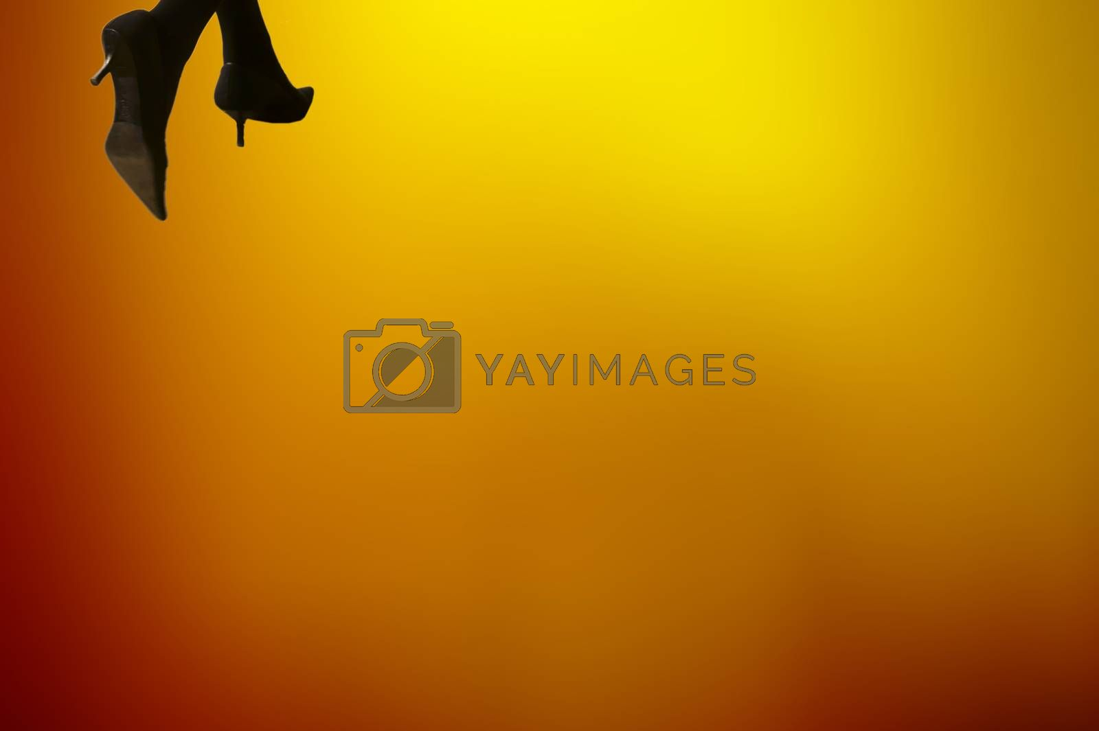The detail of women's legs with high heels in front of a flame-colored background.