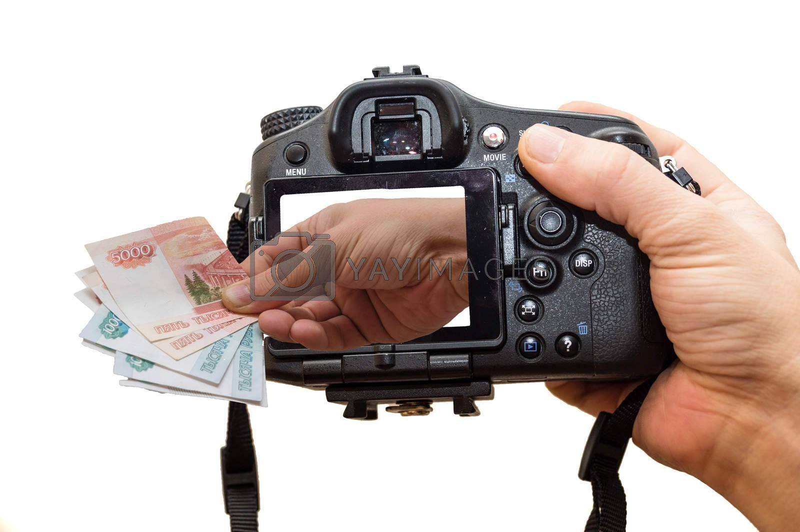 The photo depicts a camera and a hand full of money