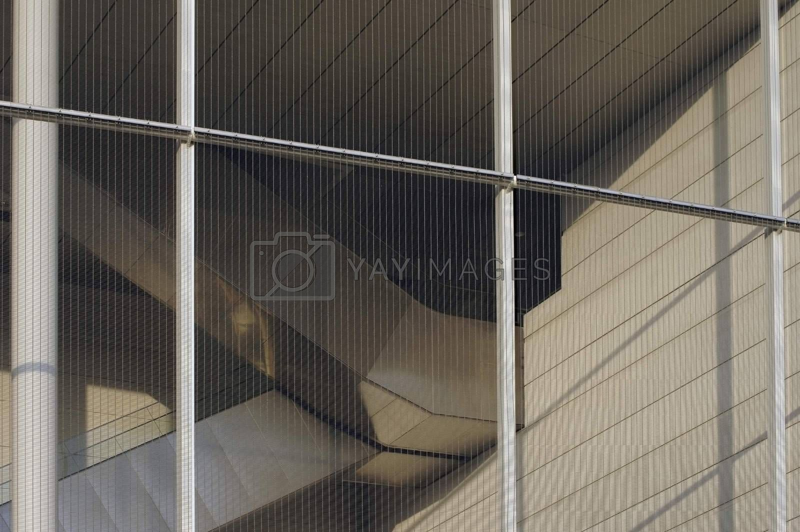 The bottom view of a edgy duct of a public building behind a mesh fence.