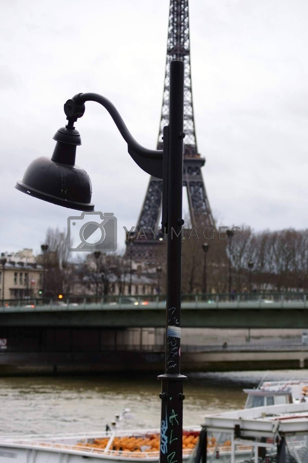 A boat for boat trips is located behind a lantern on the banks of the river Seine with the Eiffel Tower in the background.