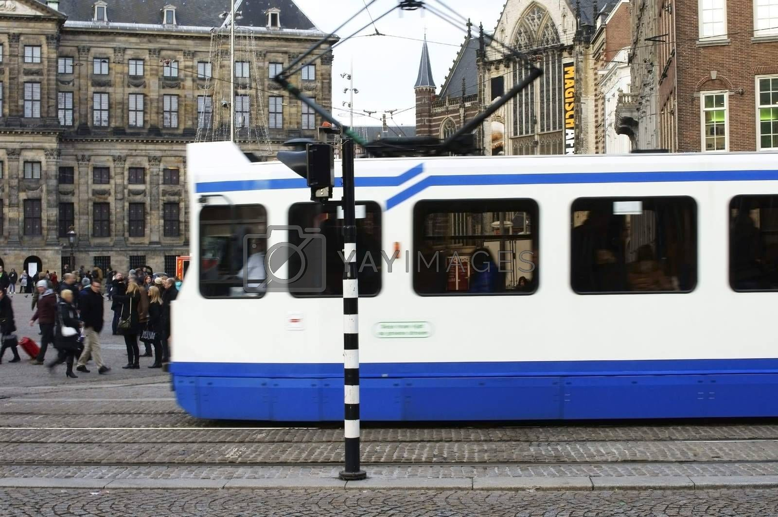 Amsterdam, Netherlands - December 29, 2014: Group of people and a tram cross the Dam Square on December 29, 2014 in Amsterdam.