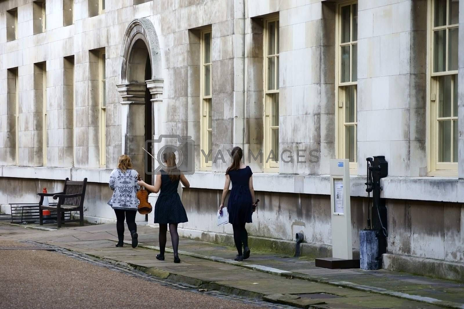 London, UK - November 29, 2014: A music teacher walks with her two students to violin lessons in an exercise room of the Royal Naval College in Greenwich on November 29, 2014 in London.