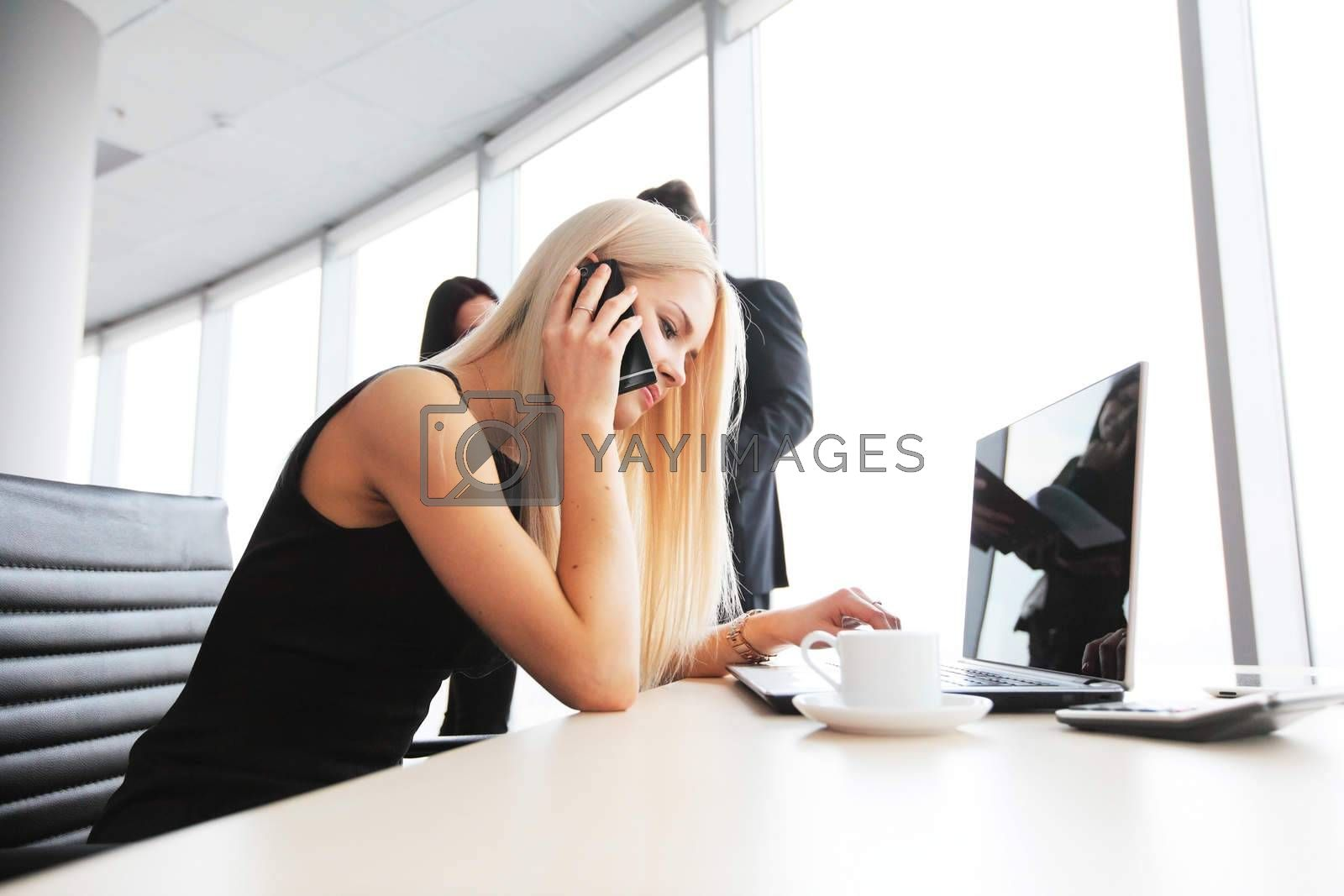 Young cute businesswoman talking on phone in office