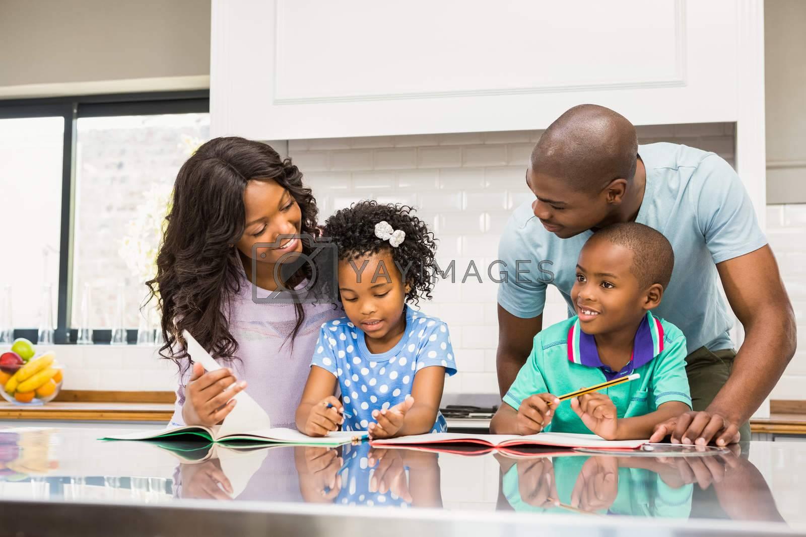 Parents helping children doing homework in the kitchen