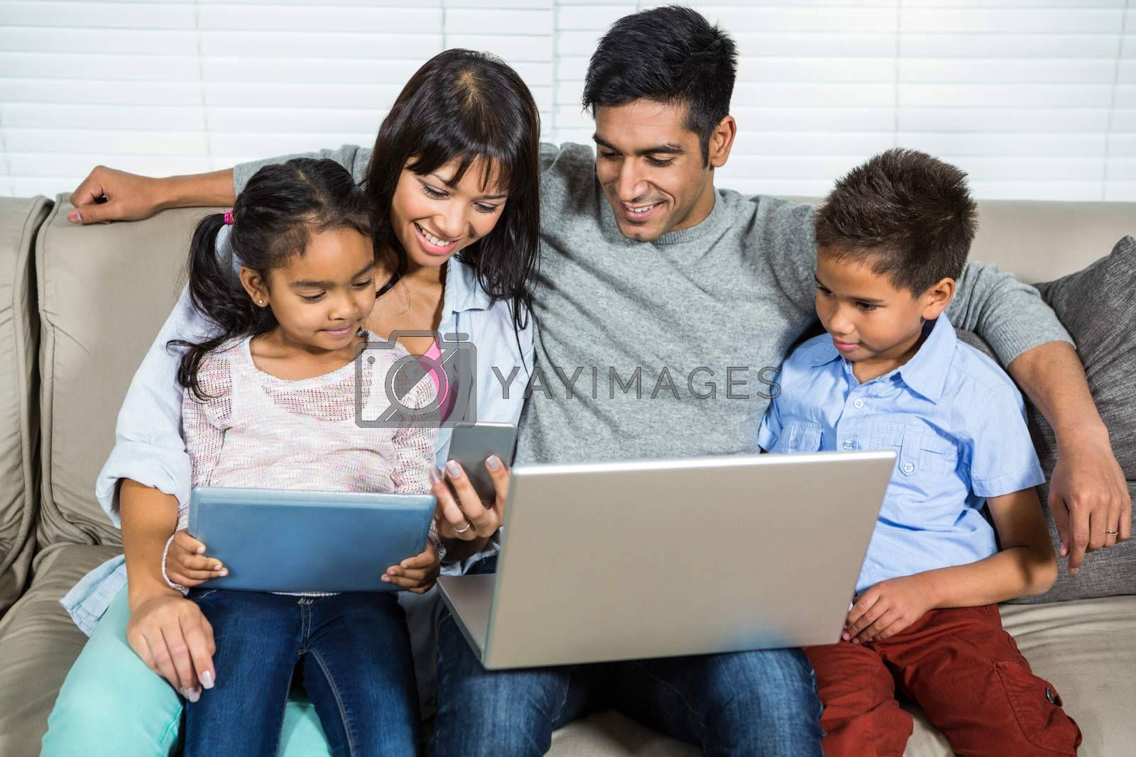 Smiling family on the sofa using technology