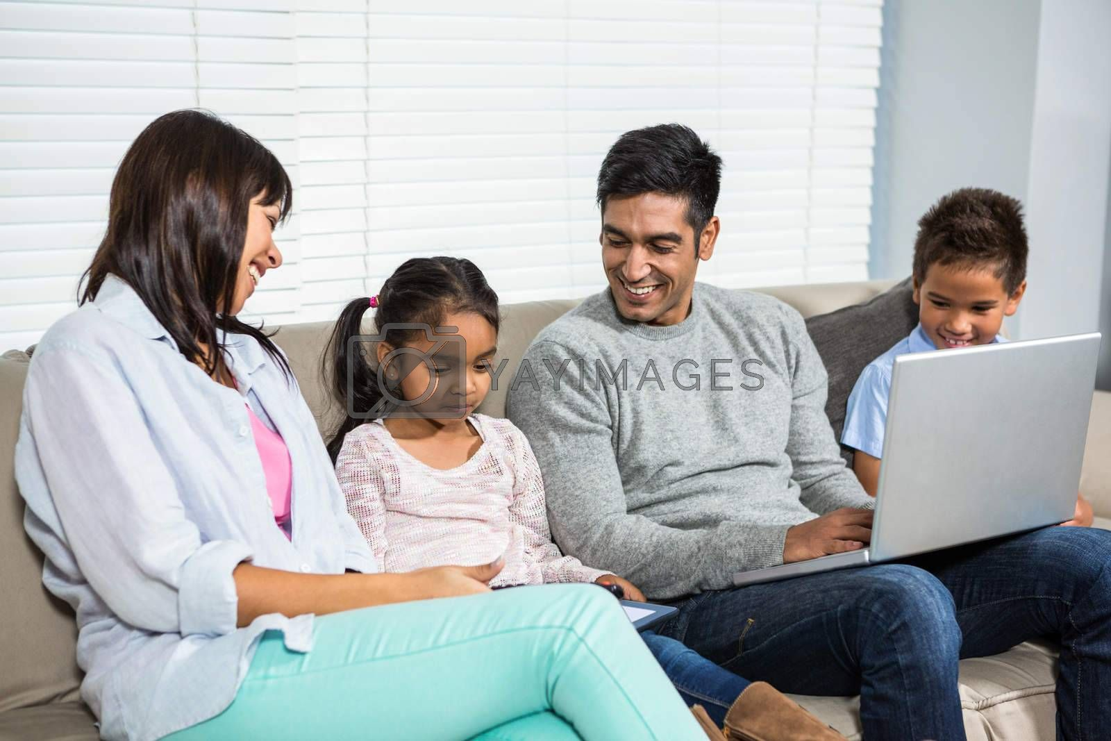 Smiling family on the sofa using laptop and tablet