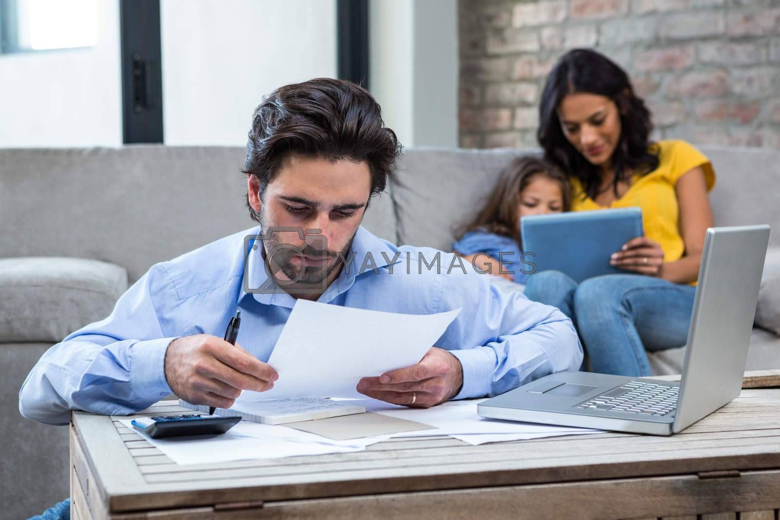 Serious man paying bills in living room while wife and daughter are on the sofa