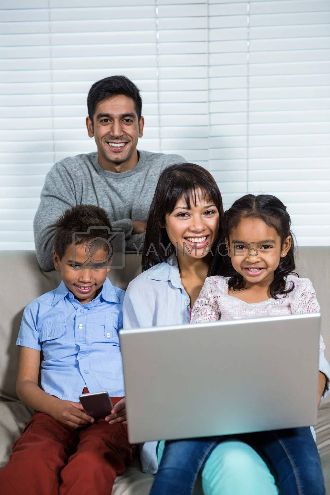 Smiling family using laptop and smartphone on the sofa in living room