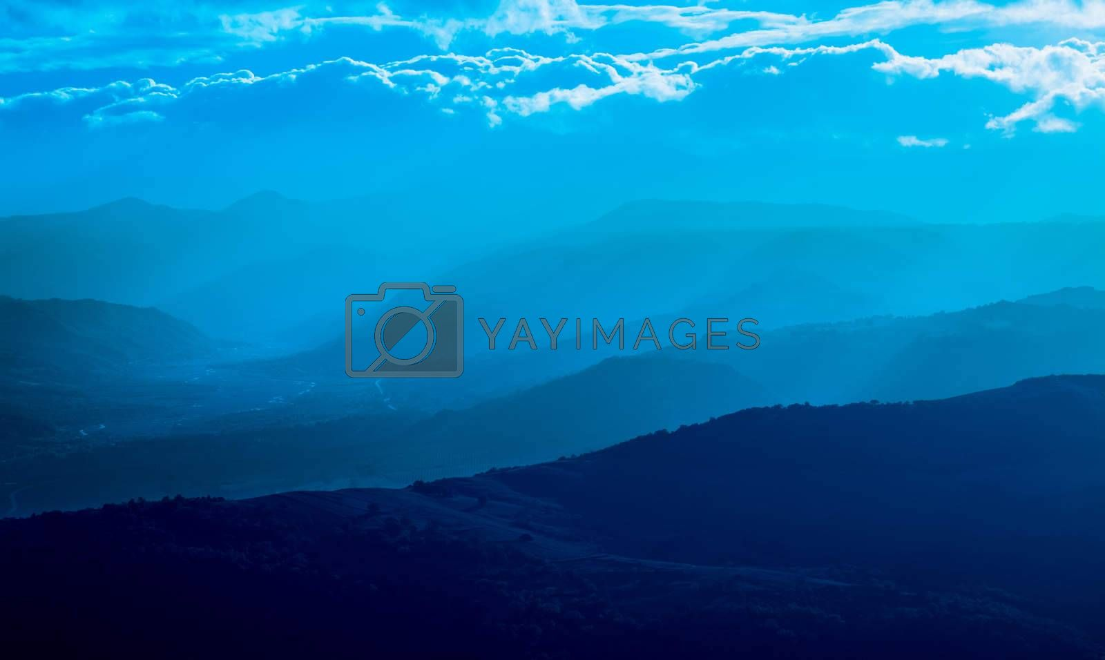 mountain silhouette with fog, natural light tint blue
