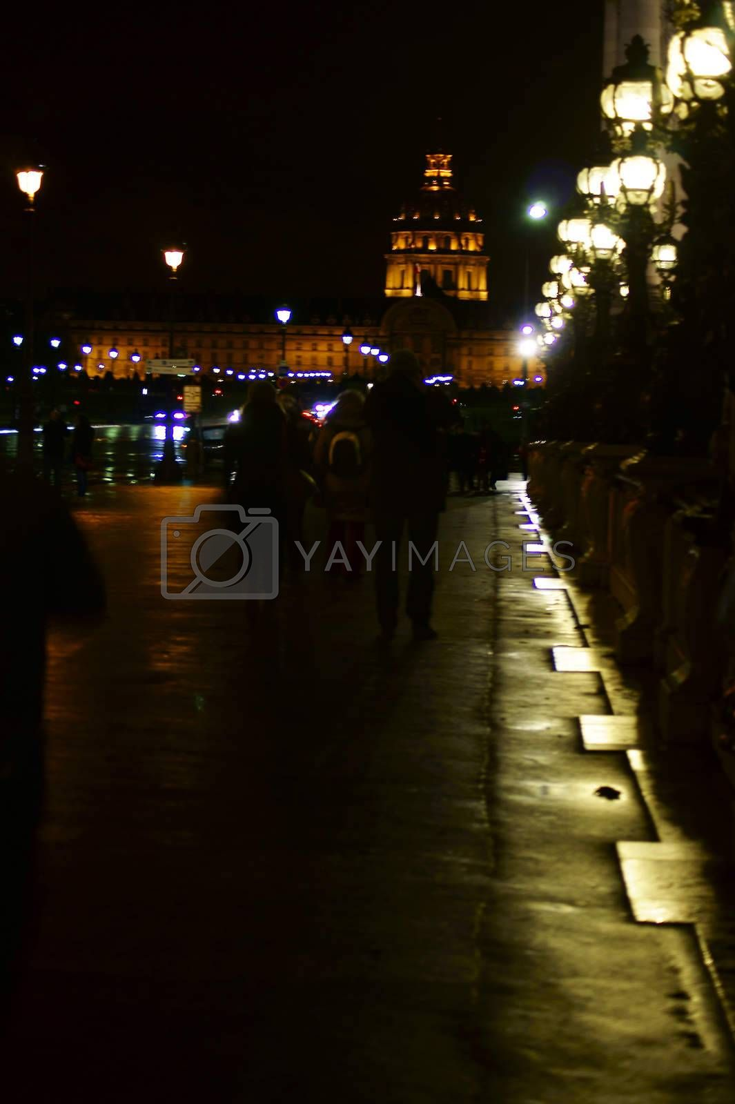 Paris, France - December 31, 2013: The Night Scene of a lighted sidewalk and a street in downtown Paris with the Invalides dome in the background on December 31, 2013 in Paris.