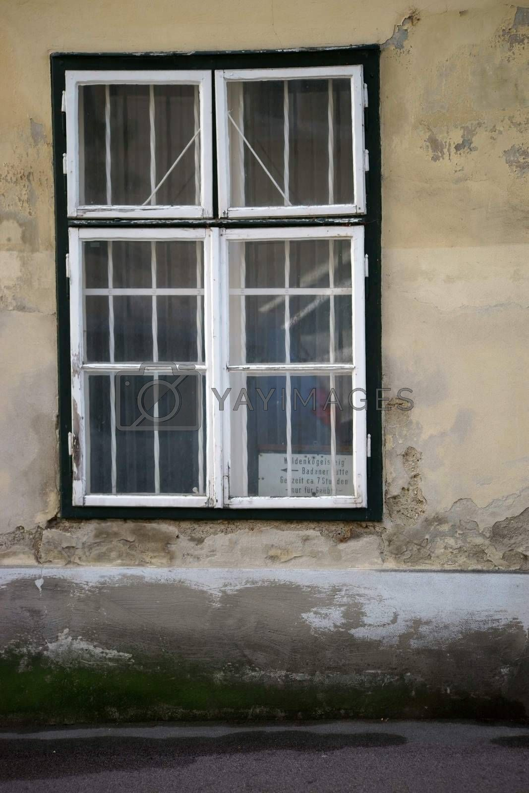 An old nostalgic wooden window in a prominent concrete wall with traces of water.