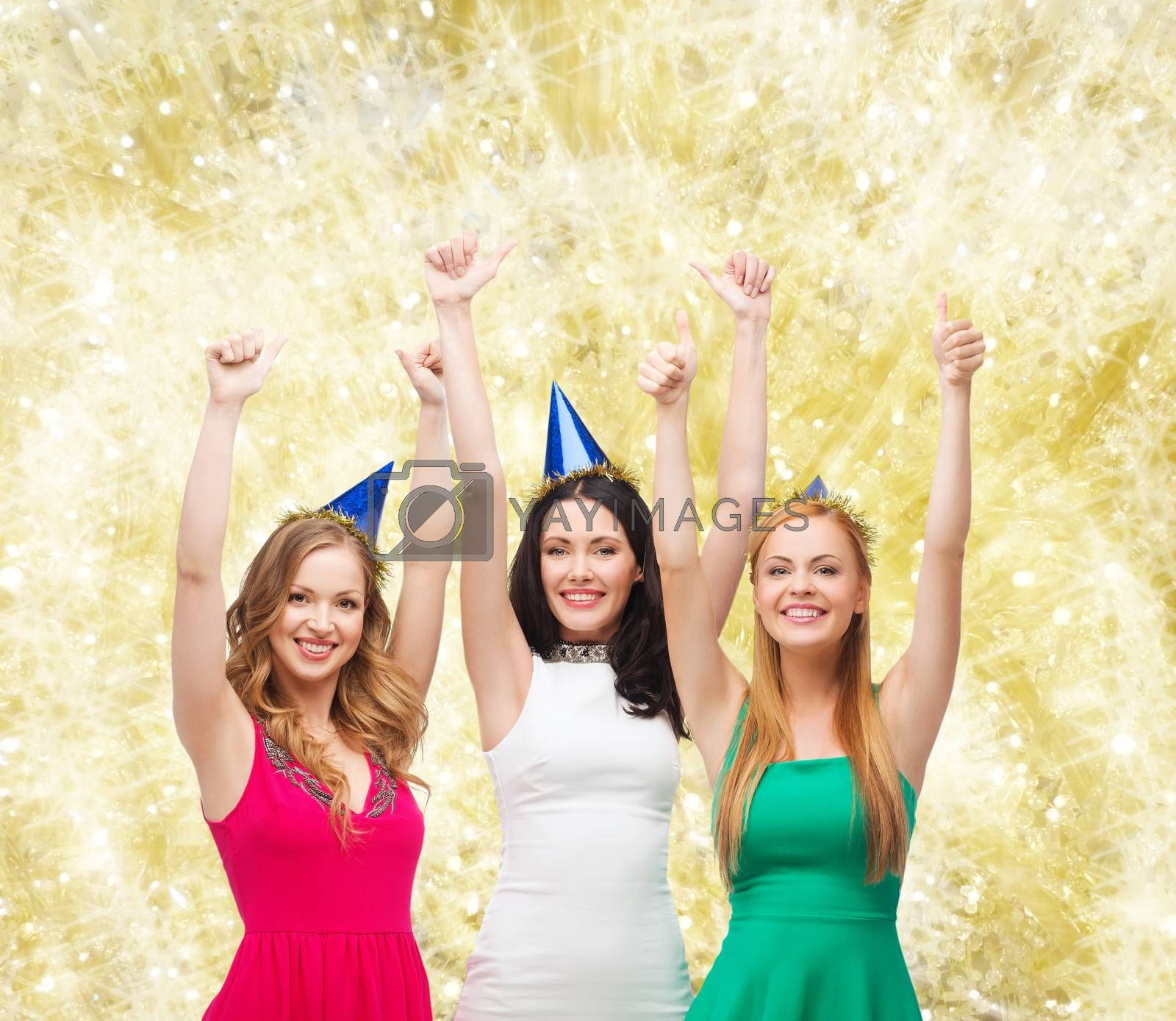 holidays, people, gesture and celebration concept - smiling women in party caps showing thumbs up over yellow lights background