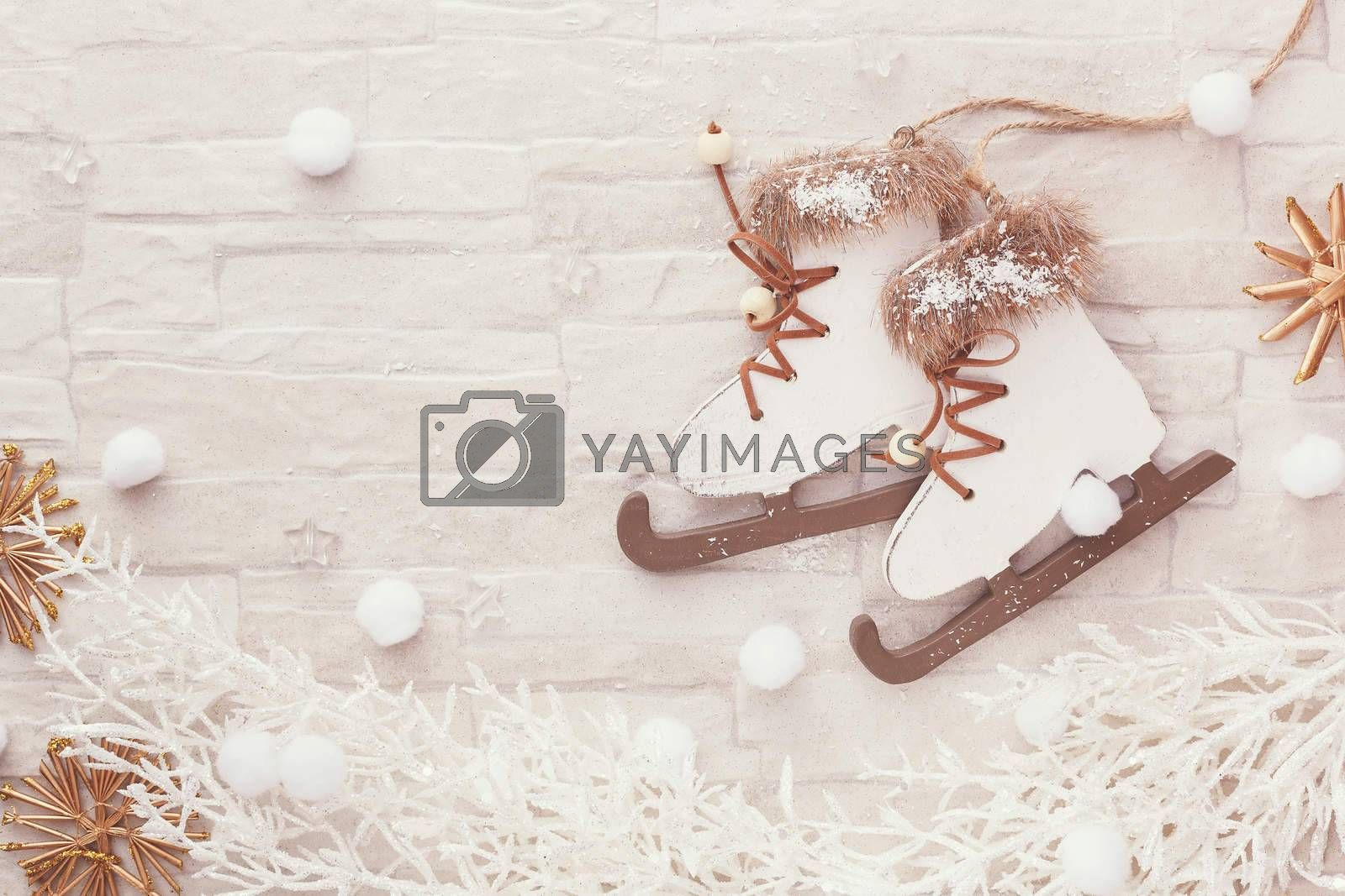 Figure skate Christmas ornament,  natural straw star ornaments and white pine twig on rustic background. Top view, blank space, vintage toned image