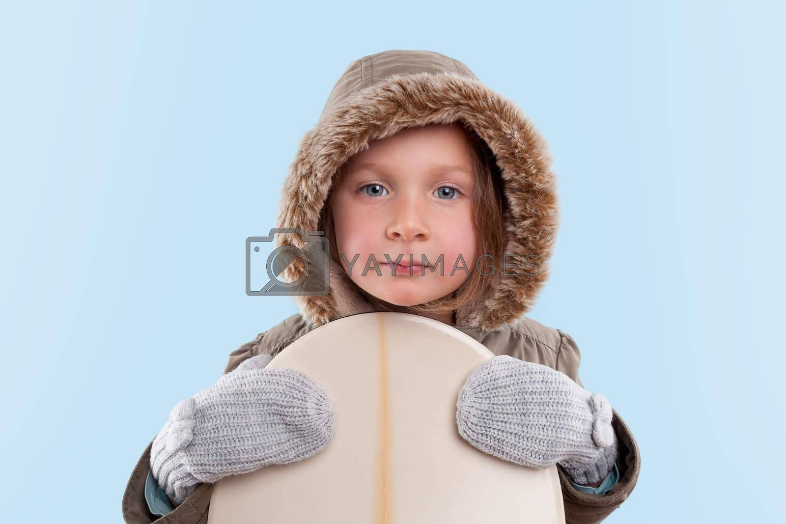 Little snowboarder. Cute little girl holding snowboard against light blue background.