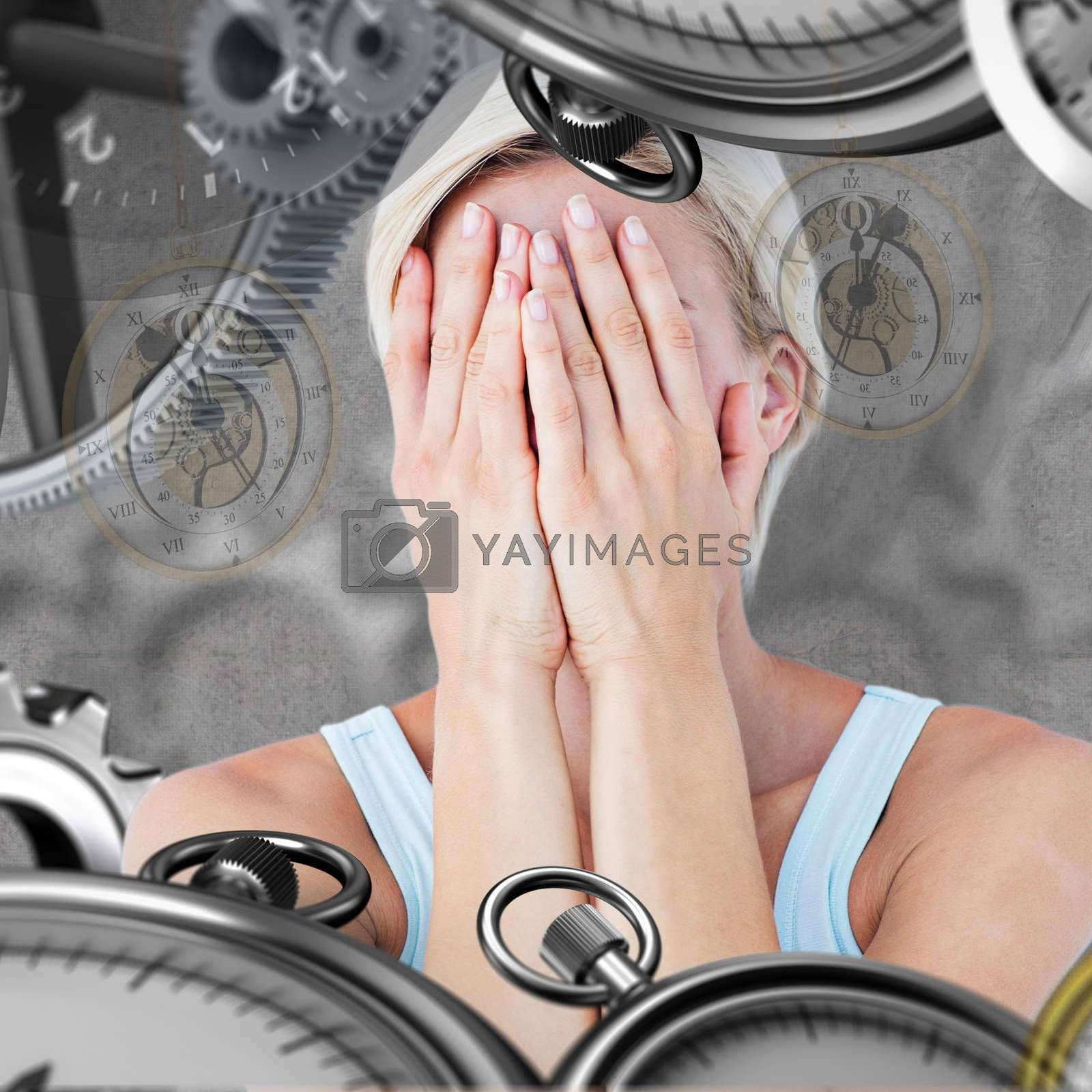 Sad blonde woman with head on hands  against grey background