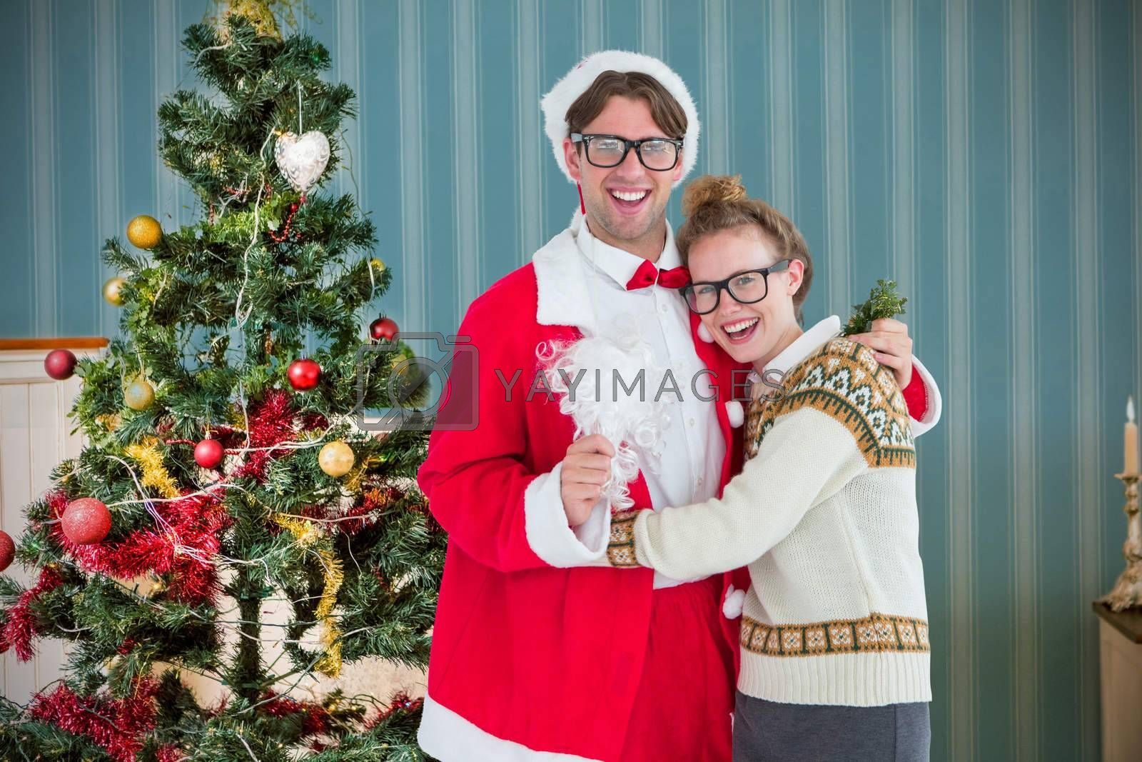 Geeky hipster in santa costume hugging his girlfriend against home at christmas time