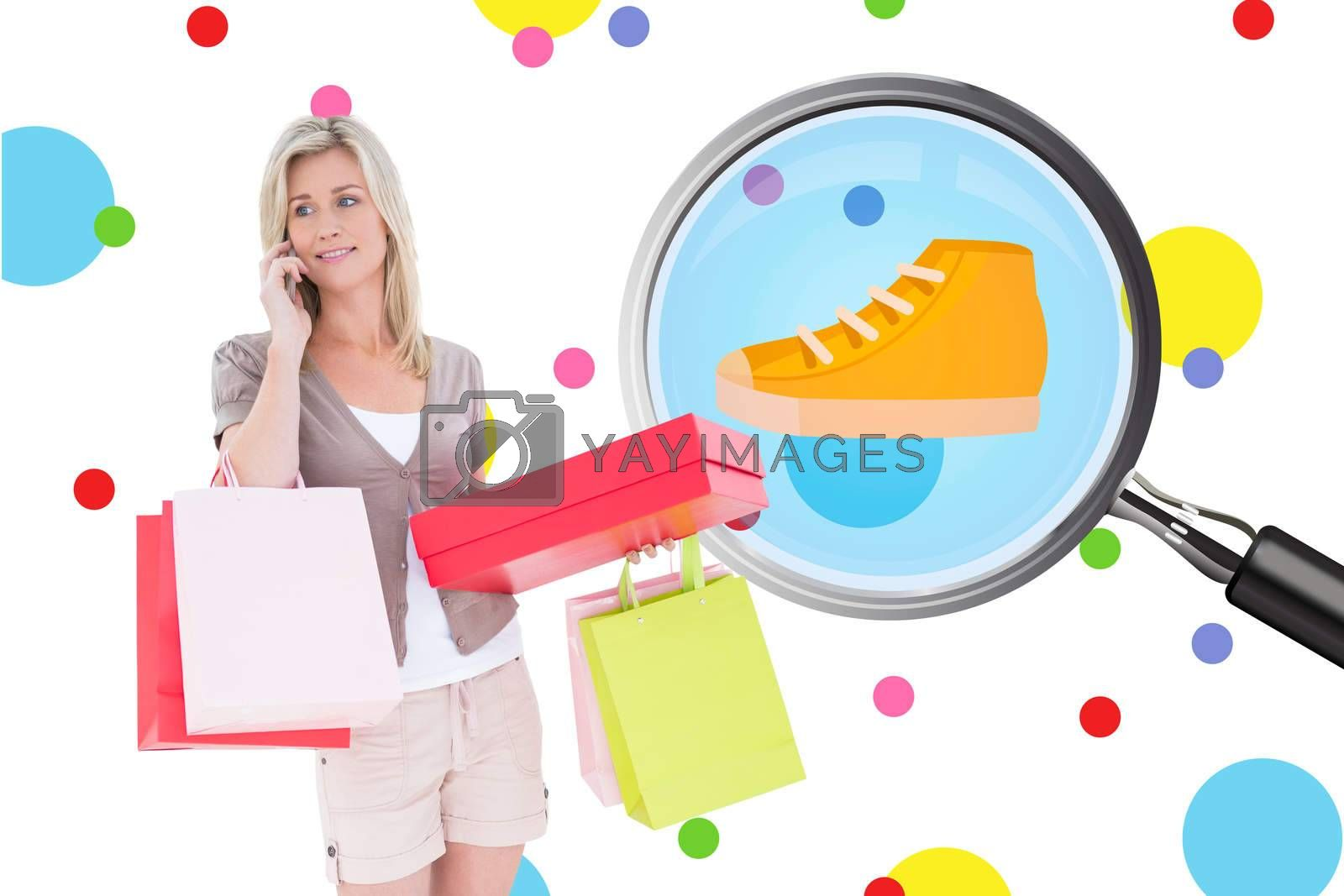 Happy blonde with shopping bags on the phone against dot pattern