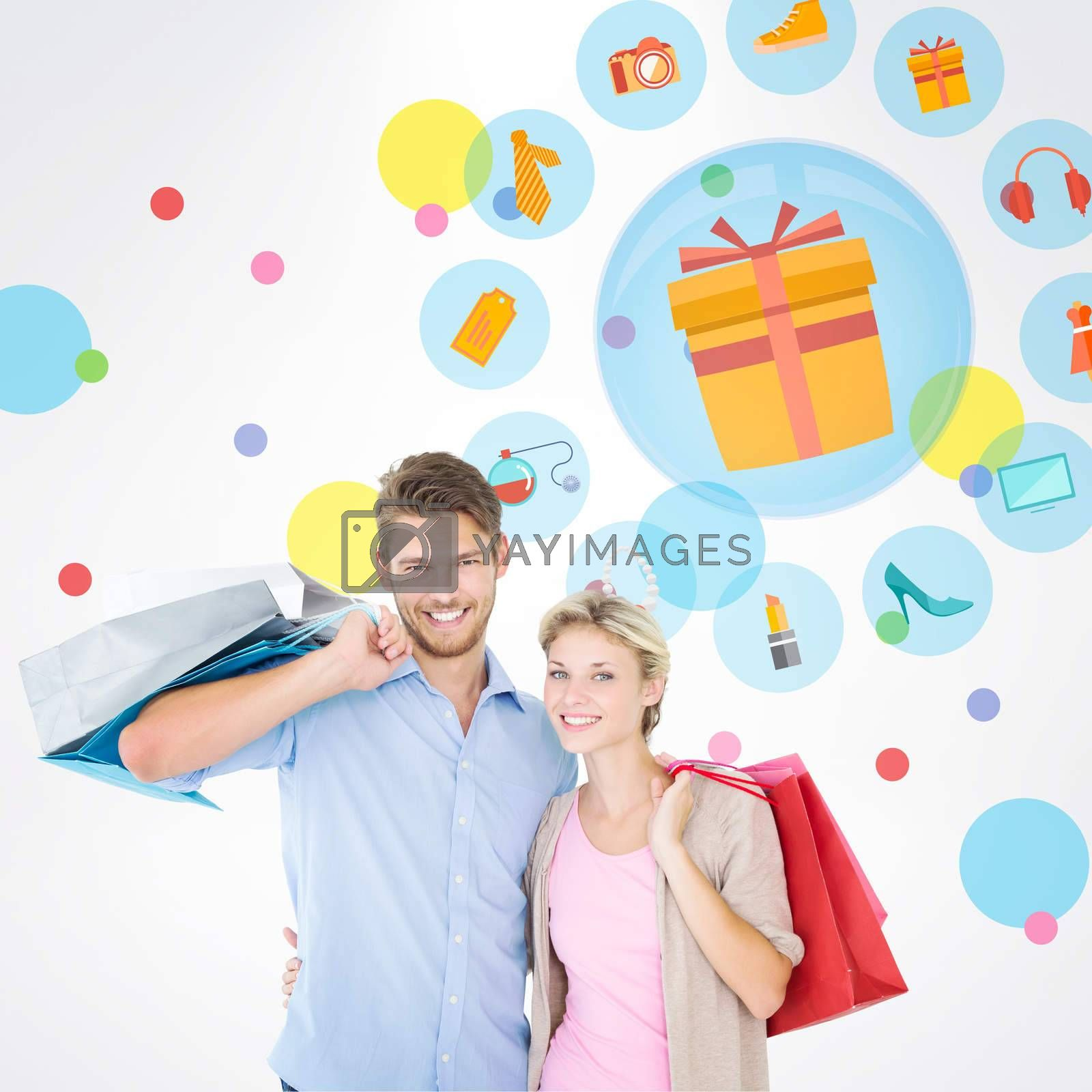 Attractive young couple holding shopping bags against dot pattern