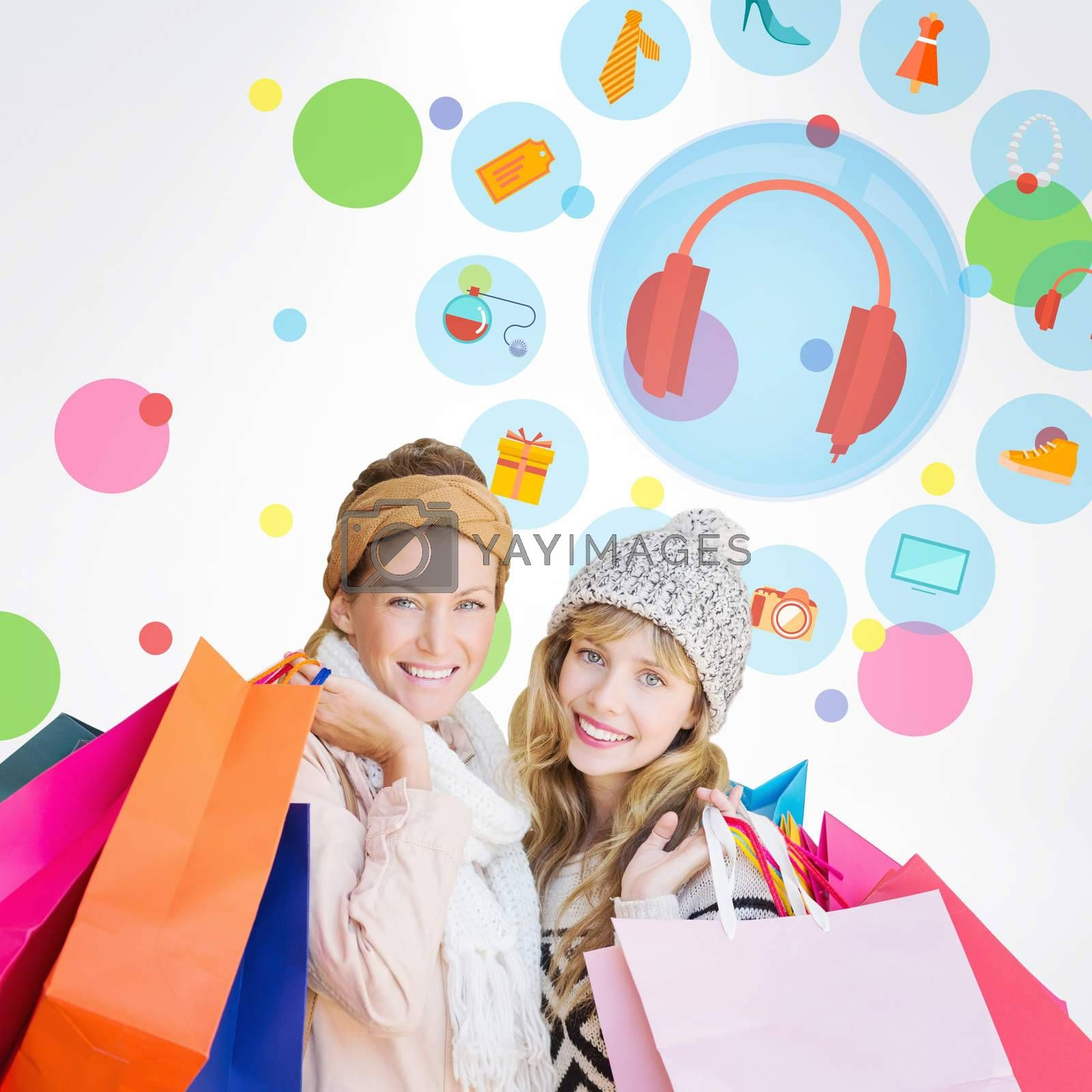 Smiling women looking at camera with shopping bags  against dot pattern