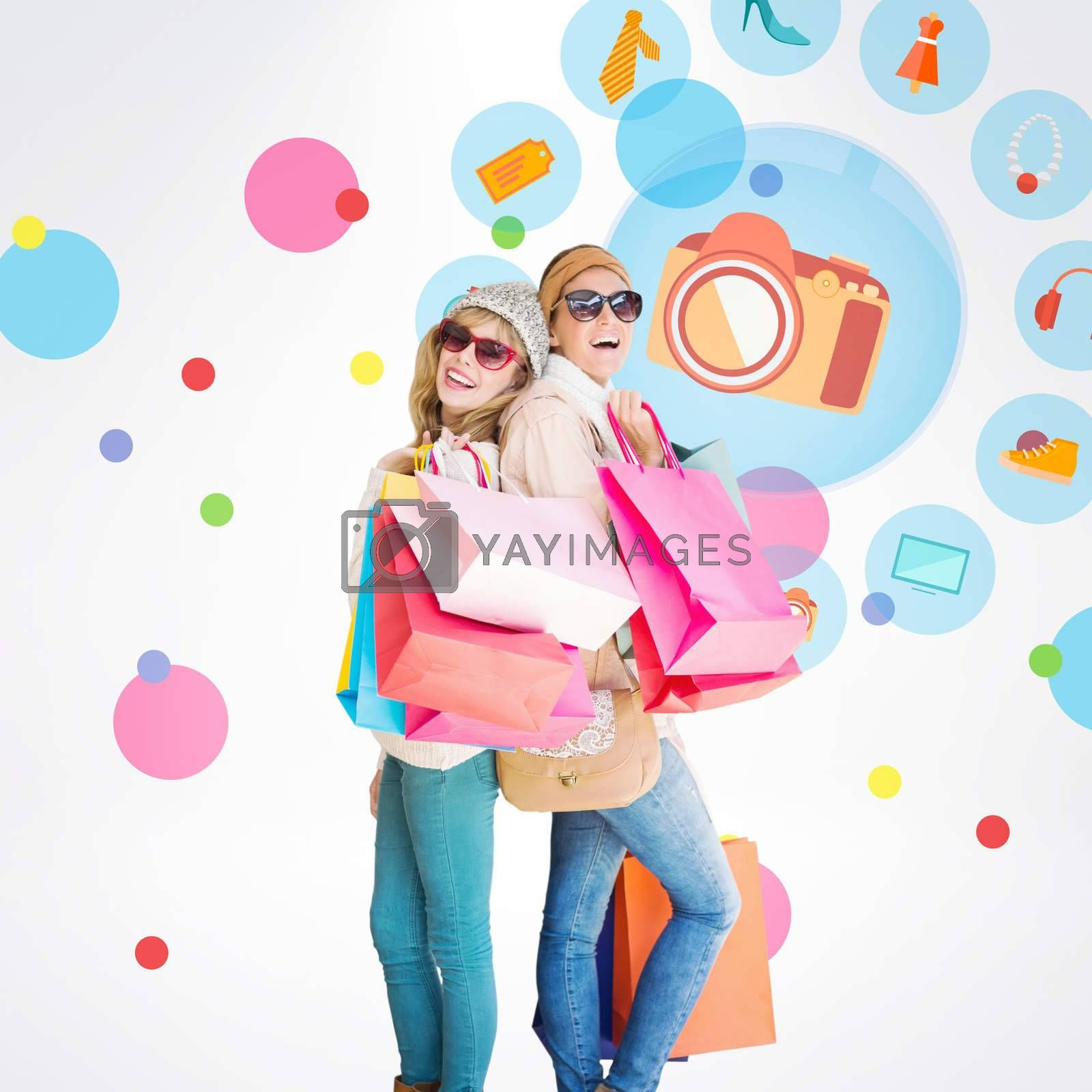Beautiful women holding shopping bags looking at camera  against dot pattern