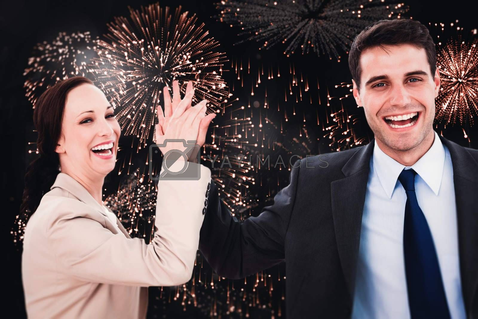Cheerful workmates doing high five against colourful fireworks exploding on black background