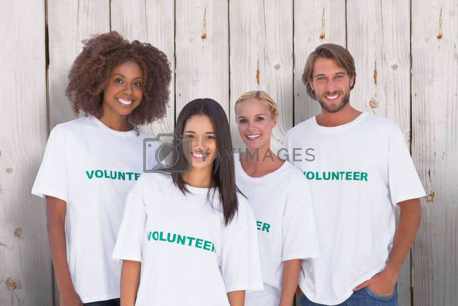 Happy group of volunteers against wooden background