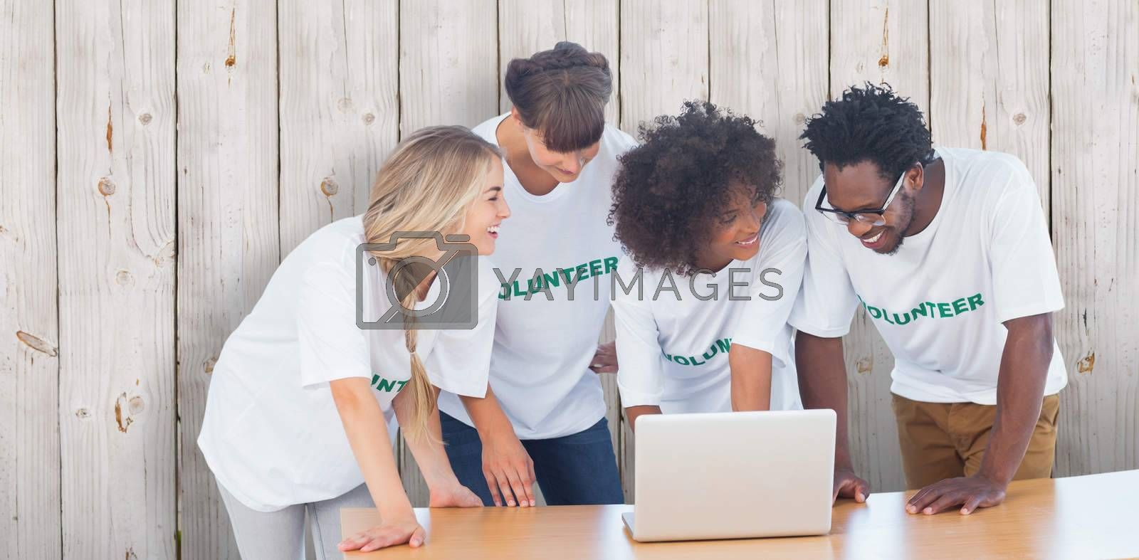 Smiling volunteers working together on a laptop against wooden background