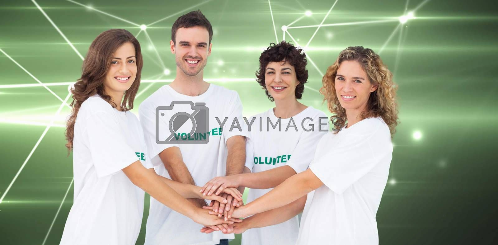 Smiling volunteer group piling up their hands against glowing geometric design