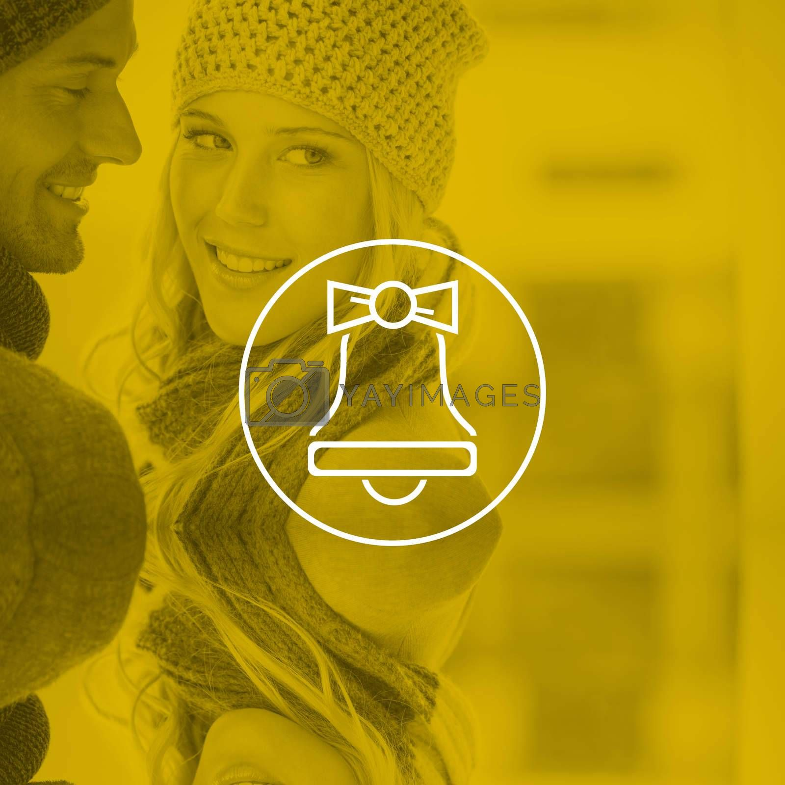Couple in warm clothing hugging against christmas bell