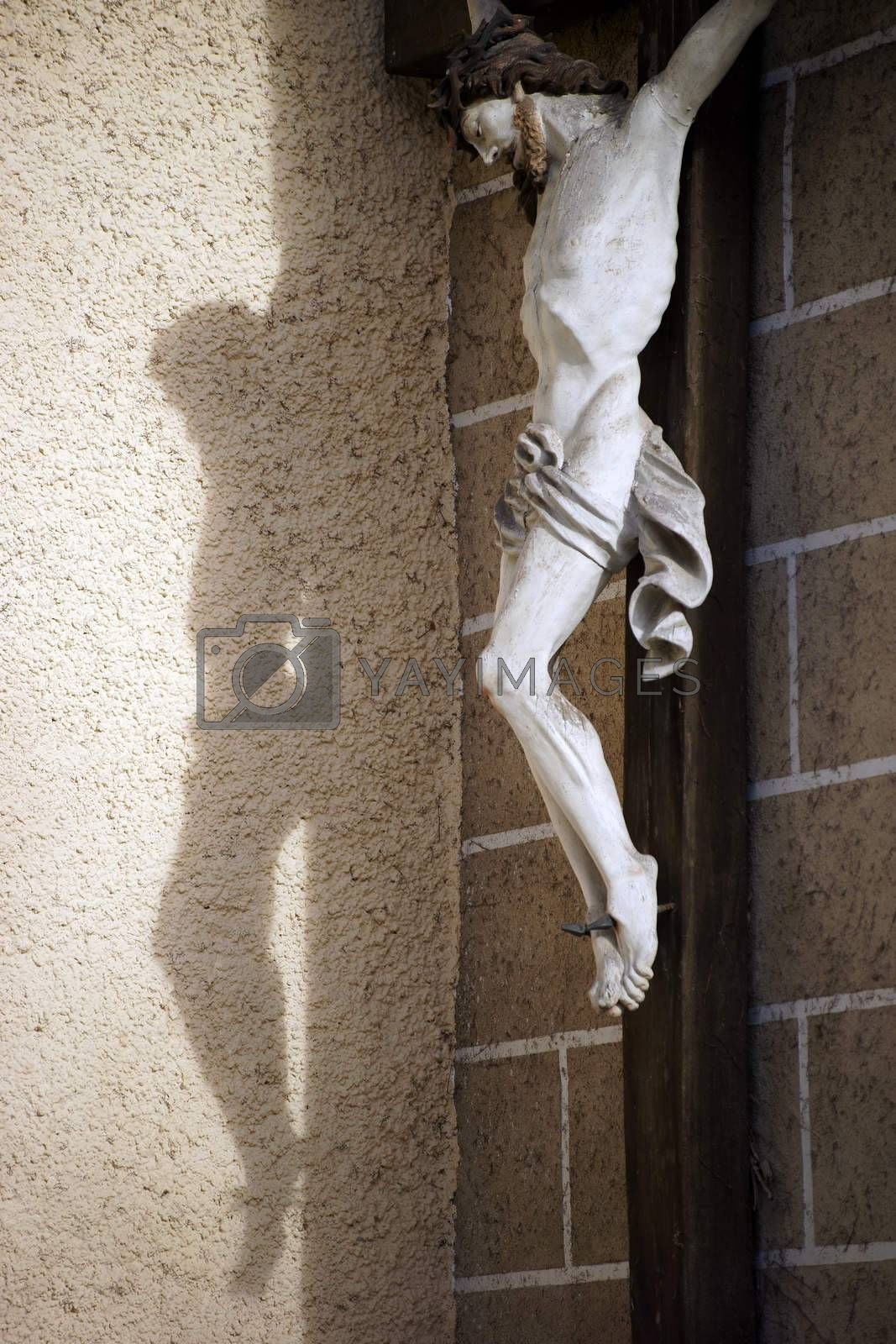Baden, Austria - November 15, 2015: A statue of Jesus on the cross casts a shadow on the wall of the Church of St. Stephan on November 15, 2015 in Baden near Vienna.