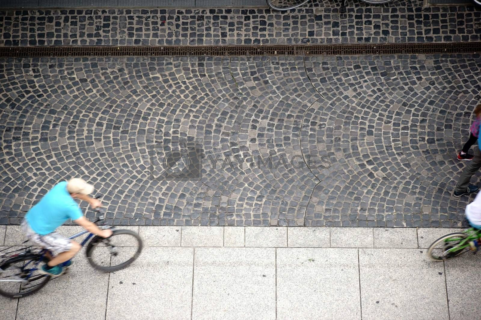 The Aerial view of a sidewalk with cobblestones and cyclists.