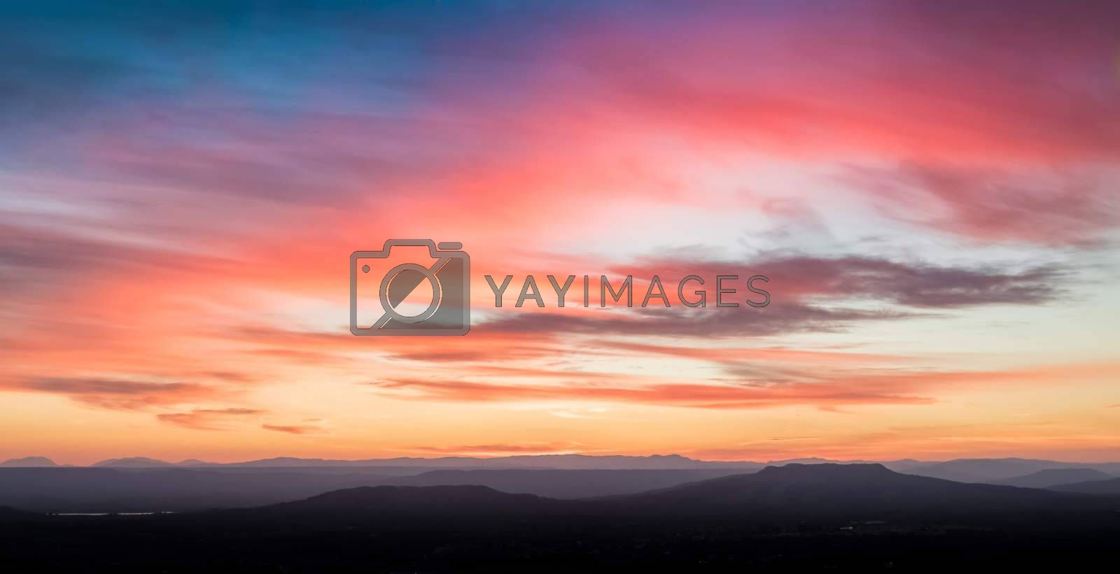 sunset scene with mountains in background, colorful sky with soft clouds