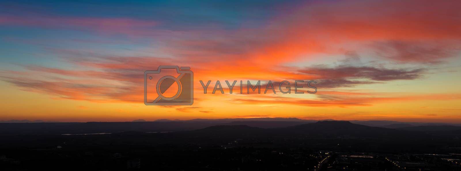 panoramic view of sunset scene with mountains in background, colorful sky with soft clouds