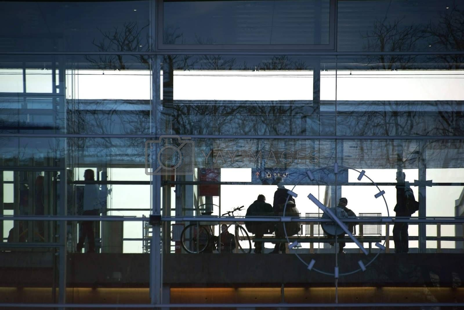 Baden, Austria - November 15, 2015: Travelers departing from the main entrance of the modern glass building of the main station on November 15, 2015 in Baden near Vienna.