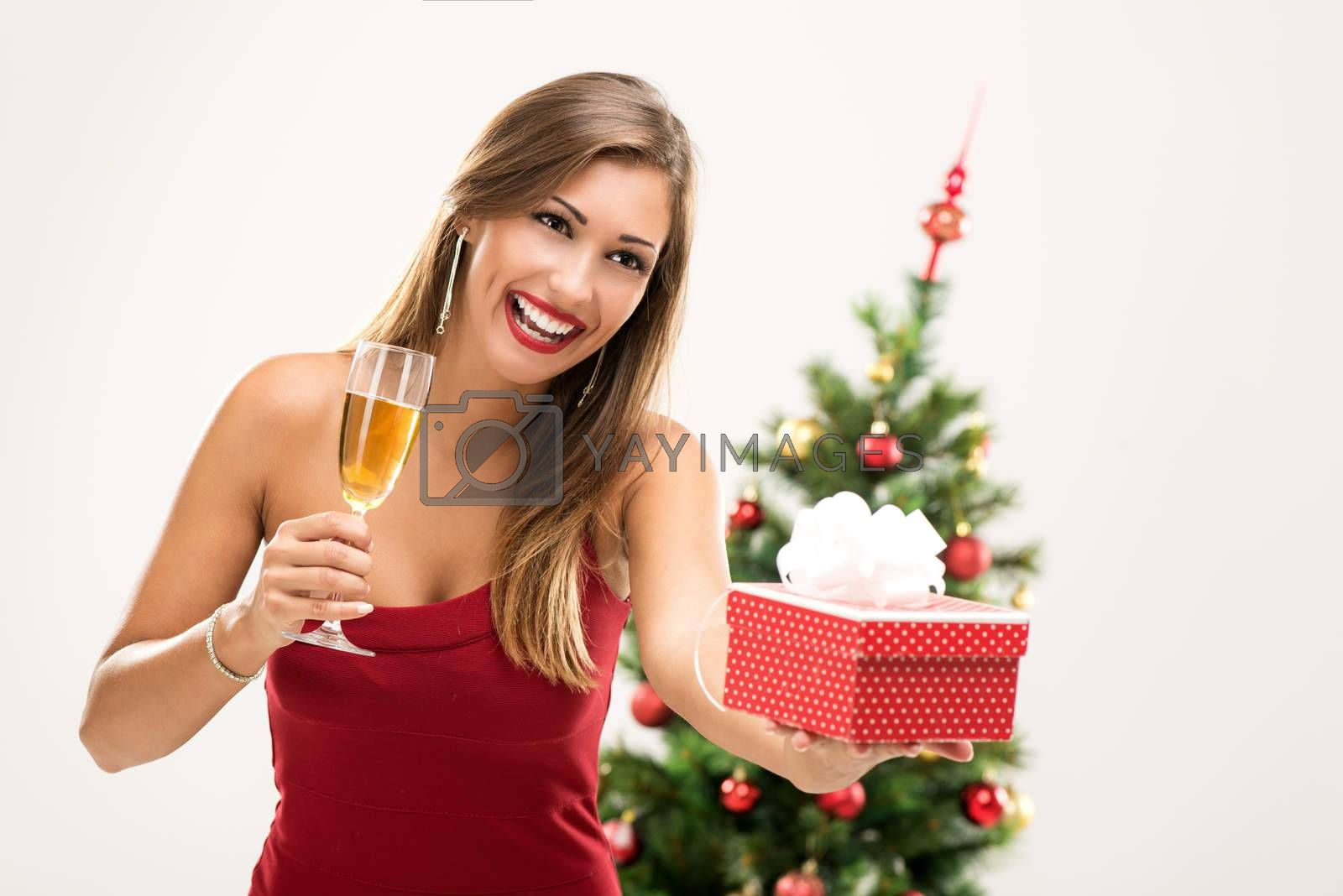 Cheerful beautiful young woman in red dress with Christmas gift toasting with champagne.