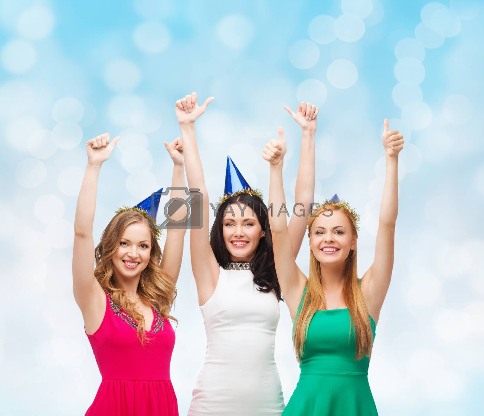 holidays, people, gesture and celebration concept - smiling women in party caps showing thumbs up over blue lights background