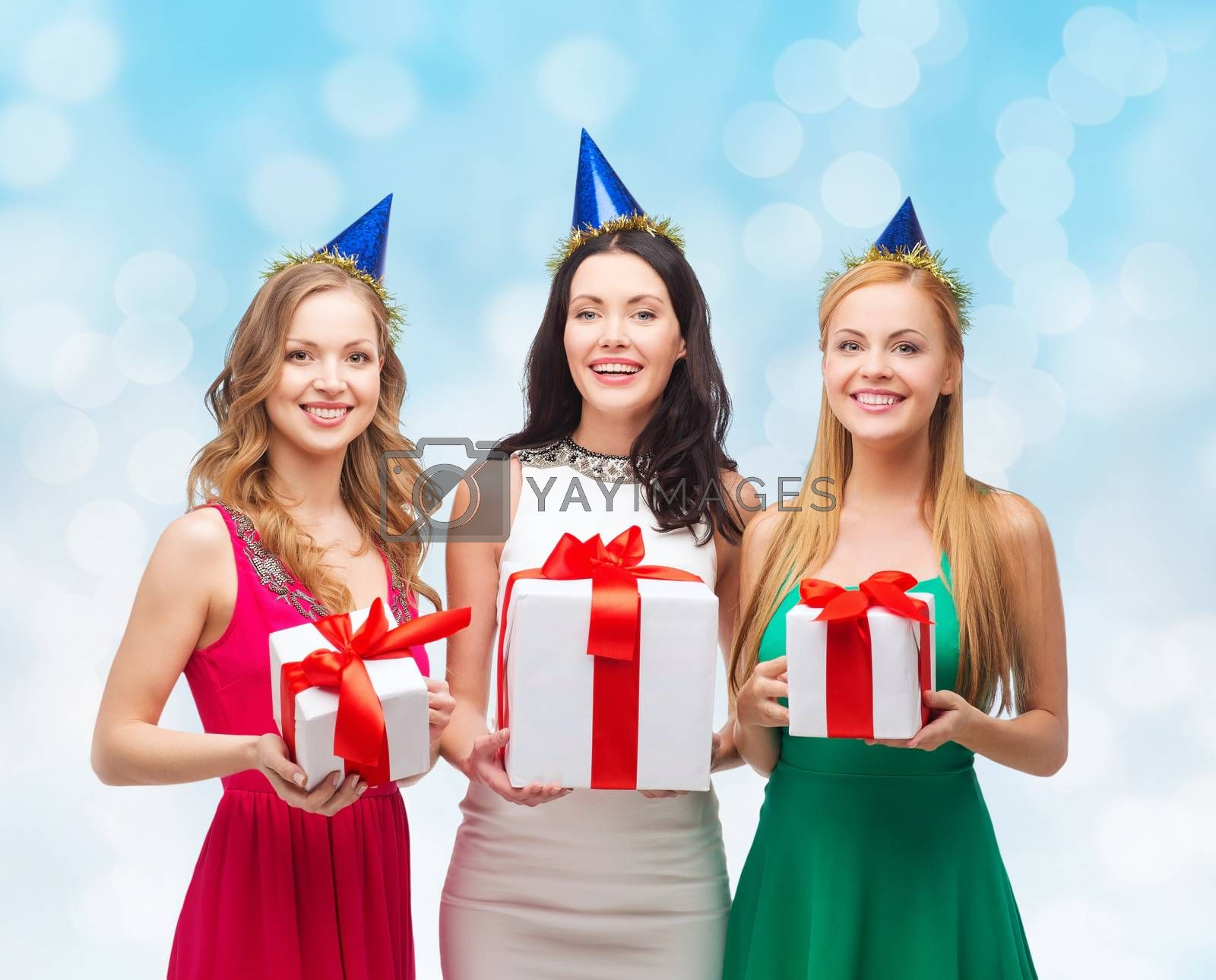 presents, holidays, people and celebration concept - smiling women in party caps with gift boxes over blue lights background